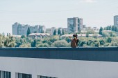 "Постер, картина, фотообои ""african american man gesturing with raised hands while standing on rooftop of building"""