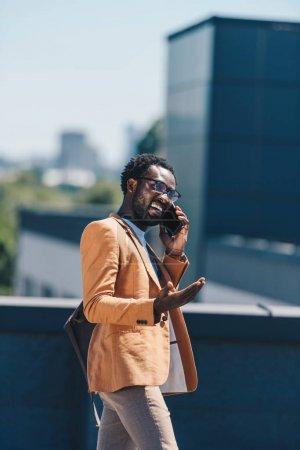 emocionado hombre de negocios afroamericano hablando en el teléfono inteligente y el gesto en la azotea
