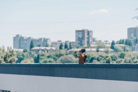 Photo pour Homme afro-américain geste avec les mains levées tout en se tenant sur le toit avec des arbres verts et ciel bleu sur le fond - image libre de droit
