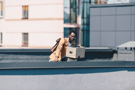 Photo for Upset businessman looking down rooftop while holding cardboard box - Royalty Free Image