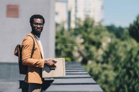 homme d'affaires afro-américain réfléchi tenant boîte en carton et regardant loin tout en se tenant sur le toit