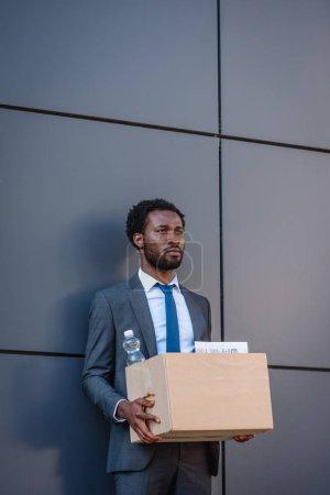 Photo pour Rejeté, bouleversé homme d'affaires afro-américain tenant boîte carton et regardant loin tout en restant près du mur - image libre de droit