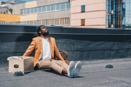 Photo for Depressed, fired african american businessman looking up while sitting on rooftop near carton box - Royalty Free Image