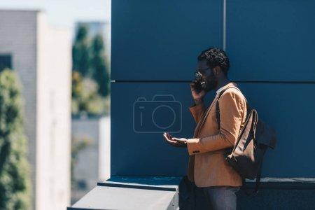 Photo pour Homme d'affaires afro-américain souriant parlant sur smartphone et gestualisant tout en se tenant sur le toit - image libre de droit