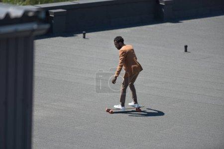 Photo pour Afro-américain homme d'affaires équitation longoard sur toit ensoleillé - image libre de droit