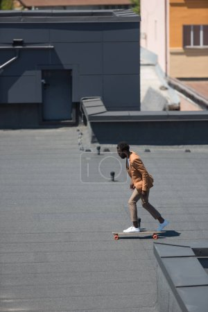 Photo for Stylish african american businessman riding longboard on sunny rooftop - Royalty Free Image