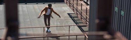 Photo pour Plan panoramique de l'homme d'affaires afro-américain longboard sur le toit ensoleillé - image libre de droit