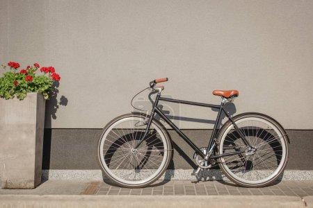 Photo pour Vélo et fleur rouge dans le pot de fleur près du mur gris sur la rue - image libre de droit
