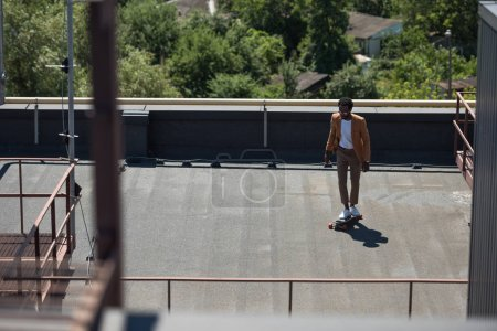 selective focus of stylish african american businessman riding longboard on sunny rooftop