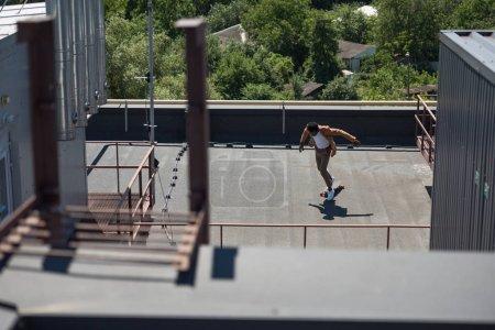 Foto de Enfoque selectivo del empresario afroamericano longboarding en la azotea soleada - Imagen libre de derechos