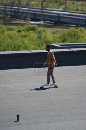 african american businessman riding longboard on sunny rooftop with railways and trains on background