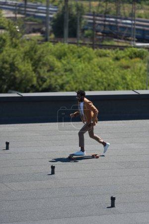 Photo pour Homme d'affaires américain africain élégant conduisant le longboard sur le toit ensoleillé - image libre de droit