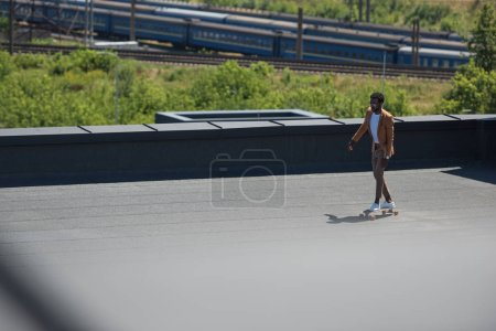 selective focus of african american businessman riding longboard on sunny rooftop with railways and trains on background