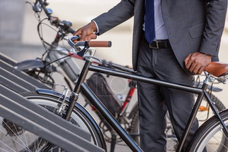 partial view of african american businessman taking bicycle from parking