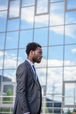 confident african american businessman in suit walking along building with glass facade
