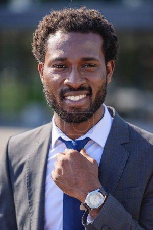 Foto de Guapo, alegre hombre de negocios afroamericano tocando la corbata y sonriendo a la cámara - Imagen libre de derechos