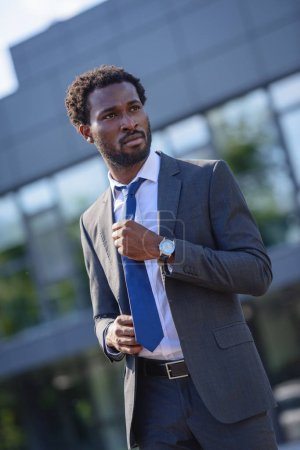confident african american businessman touching tie and looking away on street