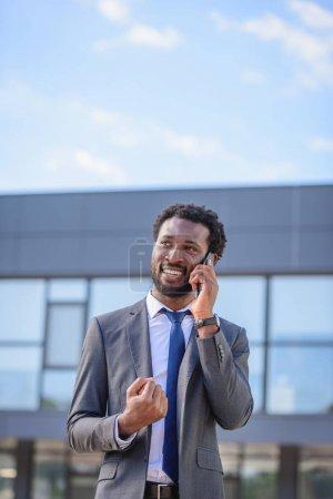 Photo pour Homme d'affaires africain heureux montrant oui geste et sourire tout en parlant sur smartphone - image libre de droit