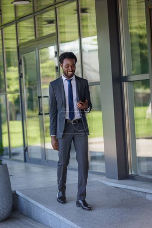 smiling african american businessman holding smartphone while walking along office buiding