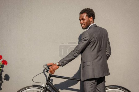 Photo pour Handsome african american businessman in suit standing by wall with bicycle - image libre de droit