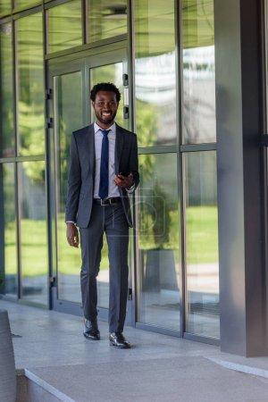 sonriente hombre de negocios afroamericano sosteniendo teléfono inteligente caminando cerca del edificio de oficinas