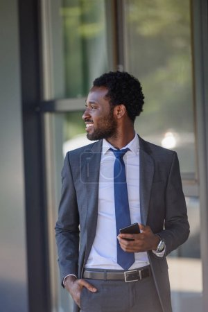 Foto de Sonriendo hombre de negocios afroamericano con teléfono inteligente que se sostiene de la mano en el bolsillo y mirando hacia otro lado - Imagen libre de derechos
