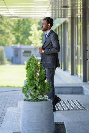Photo pour Homme d'affaires américain africain confiant regardant loin tout en restant près de l'immeuble de bureaux - image libre de droit