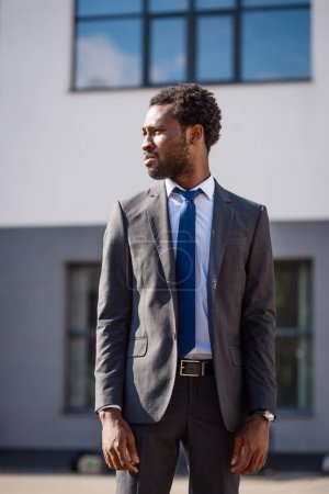 confident african american businessman in suit looking away on street