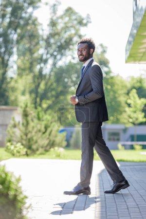 Foto de Guapo, alegre hombre de negocios afroamericano en traje sonriendo a la cámara - Imagen libre de derechos