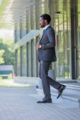 """Постер, картина, фотообои """"confident african american businessman in suit walking on stairs of office building"""""""