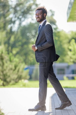 handsome, positive african american businessman in suit smiling at camera