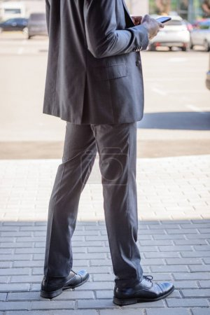 cropped view of african american businessman using smartphone on street