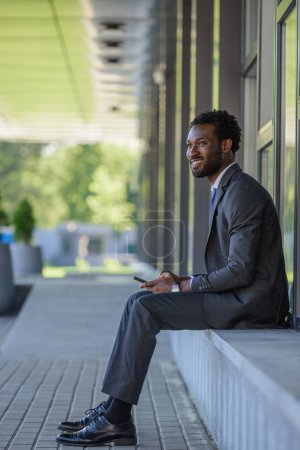 Photo for Cheerful african american american businessman using smartphone and looking away while sitting on parapet - Royalty Free Image