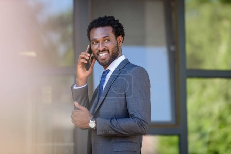 Photo for Selective focus of smiling african american businessman talking on smartphone near office building - Royalty Free Image