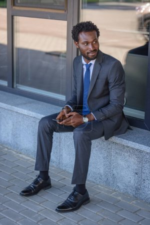 Photo for Smiling african american businessman looking away while sitting on parapet and holding smartphone - Royalty Free Image