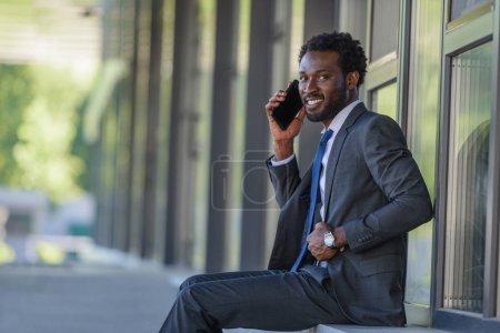 Photo pour Homme d'affaires américain aftrican gai parlant sur le smartphone et souriant à l'appareil-photo tout en s'asseyant sur le parapet - image libre de droit