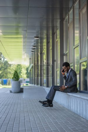 Photo for Smiling african american businessman talking on smartphone while sitting near office building - Royalty Free Image