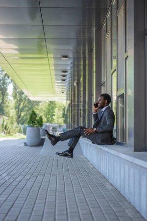 Photo pour Homme d'affaires américain africain gai parlant sur le smartphone tout en s'asseyant près de l'immeuble de bureaux - image libre de droit