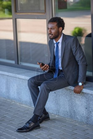 Photo for Thoughtful african american businessman holding smartphone while sitting on parapet - Royalty Free Image