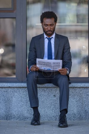 Photo for Attentive african american businessman reading newspaper while sitting near office building - Royalty Free Image