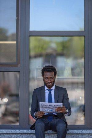 Photo pour Homme d'affaires américain africain souriant affichant le journal tout en s'asseyant près de l'immeuble de bureau avec la façade en verre - image libre de droit