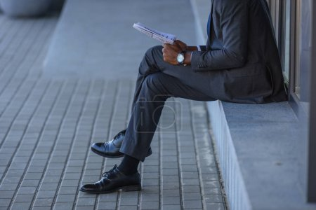 cropped view of african american businessman reading newspaper while sitting on parapet