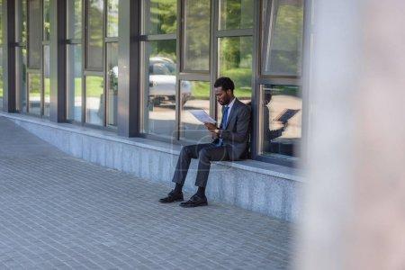 Photo pour Foyer sélectif du journal de lecture américain africain concentré tout en s'asseyant sur le parapet de l'immeuble de bureaux - image libre de droit