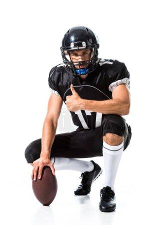 Photo pour Joueur américain de football avec la bille faisant le pouce vers le haut signent sur le blanc - image libre de droit