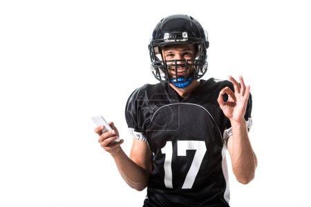 Photo pour Joueur de football américain avec le smartphone et le signe correct d'isolement sur le blanc - image libre de droit