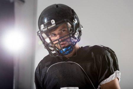 Photo pour Joueur américain de football dans le casque sur le gris avec le rétro-éclairé - image libre de droit