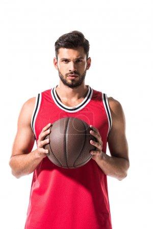 Photo pour Joueur sportif de basket-ball retenant la bille et regardant la caméra d'isolement sur le blanc - image libre de droit