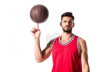 Photo pour Joueur de basket-ball tournant sur la bille de doigt et regardant la caméra d'isolement sur le blanc - image libre de droit