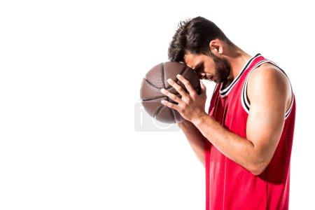 Photo pour Joueur de basket-ball athlétique dans la tête penchée uniforme sur la bille d'isolement sur le blanc - image libre de droit