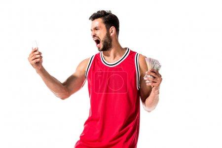 Photo pour Joueur de basket en colère tenant de l'argent et smartphone isolé sur blanc - image libre de droit